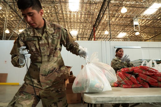 Members of the California National Guard help to bag food at FIND Food Bank in Indio, Calif. on Monday, March 23, 2020 to help supply food to those affected by the coronavirus outbreak.